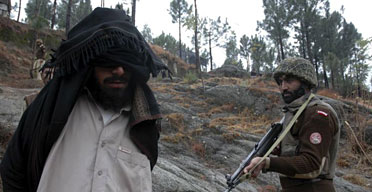 A soldier arrests a suspected militant in Pakistan