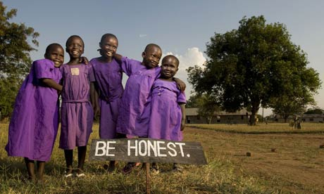 Children from the Tiriri primary school in Katine stand behind one of the many signs on the school grounds that aim to promote good behaviour