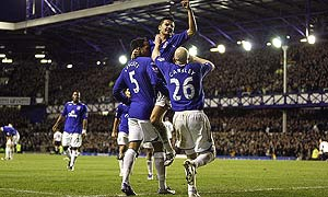 Everton's Tim Cahill (centre) celebrates after scoring with team mates Lee Carsley (right) and Joleon Lescott during a match at Goodison Park.