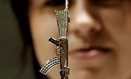 An assistant shows a gold tie clip in the form of a Russian Kalashnikov assault rifle during a jewellery exhibition, Junwex, in St Petersburg
