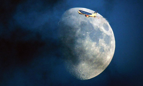 A bmi Airbus plane flying past the moon through a cloudy sky over London