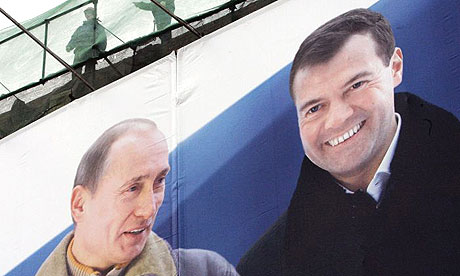Building engineers work above a huge election poster depicting Vladimir Putin (l) and his likely successor as president, Dmitry Medvedev