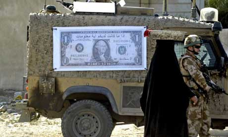 An Iraqi woman walks past a British soldier and military vehicle with a poster of a dollar bill with the Arabic writing: You can get some money, in exchange for some information
