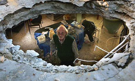 Silvio Grinberg peers through a hole in the ceiling of his living room caused by a Grad rocket fired by Palestinian militants from the Gaza Strip at the southern Israeli costal city of Ashkelon