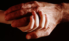Elderly man and boy hold hands. Photograph: Henry Wo