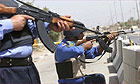 Iraqi police take defensive positions in Basra during a gun battle with Shia militants.