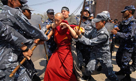 Nepalese policemen arrest a Tibetan monk during a demonstration in front of the Chinese embassy in Kathmandu