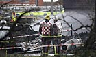 Fire crews stand in front of the wreckage of a light aircraft that crashed in a residential street in Farnborough, Kent