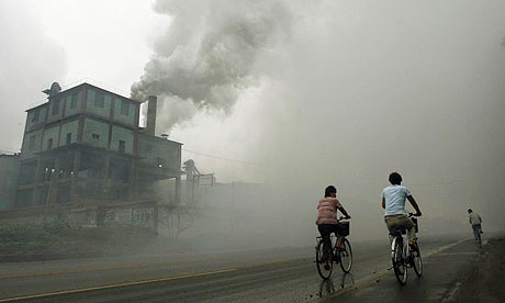 Cyclists pass through thick pollution from a factory in Yutian, 100km east of Beijing, China