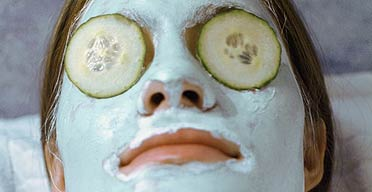 A woman recieving a spa treatment with a blue facial mask and cucumber slices on her eyes