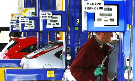 A man is warned by a sign not to pump more than £20 worth of petrol at a garage forecourt in Linlithgow, Scotland
