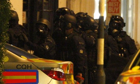 Police officers wear gas masks at siege involving gunman and armed police
