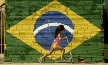A young girl plays in front of a Brazilian flag in Rio de Janeiro