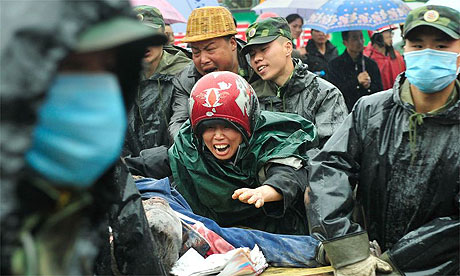 A mother mourns a Chinese soldiers carry the body of her child who was killed when a school building collapsed during the earthquake in Dujiangyan, China.