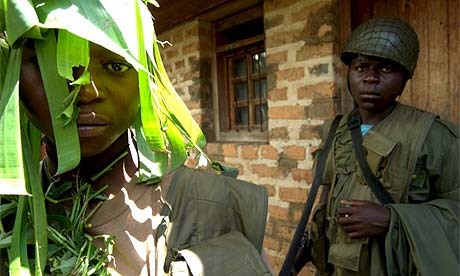 Child soldiers from the Mai-Mai militia guard the headquarters of their leader in Kisharu, Democratic Republic of Congo