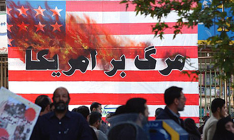 Iranians pass a US flag with a sign reading