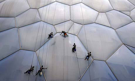 Workers clean the bubble-shaped surface of the National Aquatics Centre in Beijing in preparation for next month's Olympics