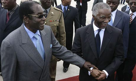 Zimbabwe's president, Robert Mugabe, welcomes the South African president, Thabo Mbeki, on his arrival in Harare