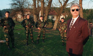 Former Bosnian Serb leader Radovan Karadzic stand surrounded by guards