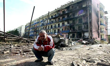 A Georgian man squats amid the rubble of a destroyed street in the town of Gori, Georgia