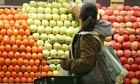 A woman selects apples while shopping in the produce section at Whole Foods in New York