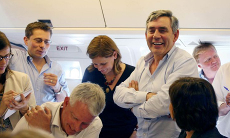 Gordon Brown jokes with the press on board to Beijing