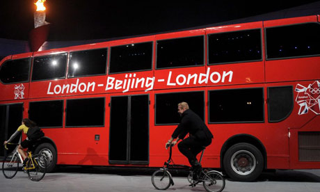 Triple gold medalist Chris Hoy rides alongside a double decker bus during the closing ceremony at the National Stadium during the 2008 Beijing Olympics