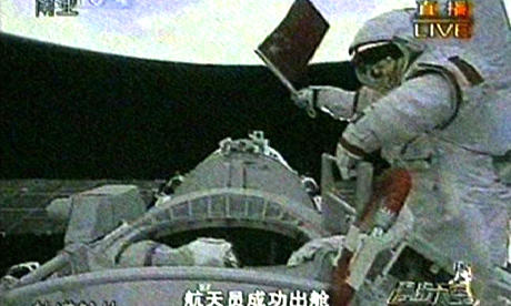Chinese astronaut Zhai Zhigang waves the national flag after exiting the Shenzhou VII spacecraft