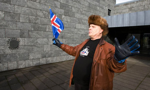 A protestor waves an Icelandic flag outside the Central Bank of Iceland