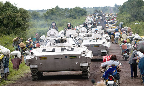 UN armoured vehicles pass refugees fleeing a camp near the east Congolese city of Goma