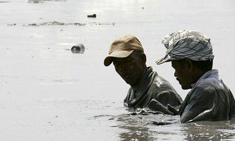 Two residents of Sidoarjo in eastern Java wade through chest-deep mud in search of possessions lost to the mud volcano