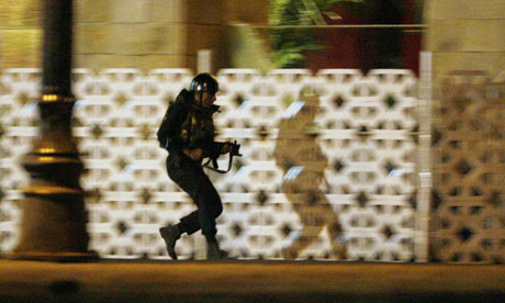 A commando takes up position during an ongoing gun battle at the Taj hotel in Mumbai
