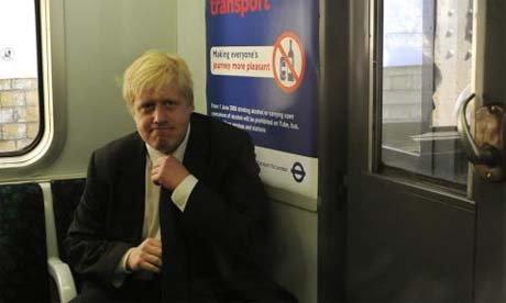 Boris Johnson adjusts his tie on an underground train