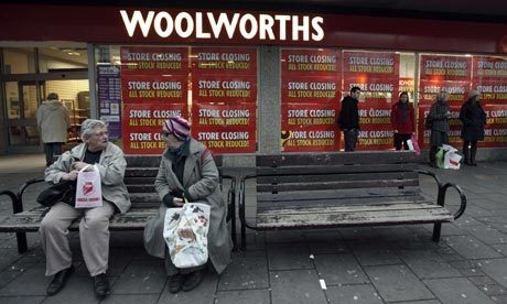 Shoppers sit outside a Woolworths branch in London
