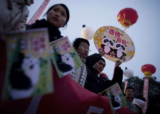 Chinese students and workers hold placards baring the names Tuan Tuan and Yuan Yuan during the send-off ceremony