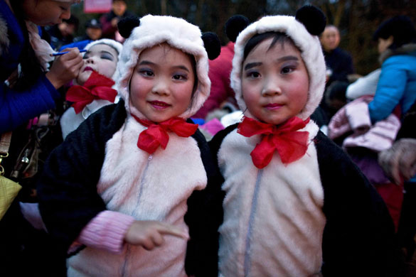Girls dressed as panda bears get ready to perform during the ceremony marking the delivery of two panda bears from China to Taiwan