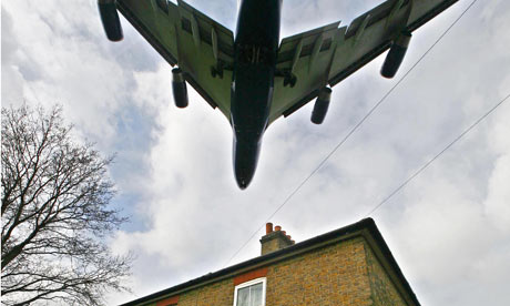 A passenger jet flies over rooftops