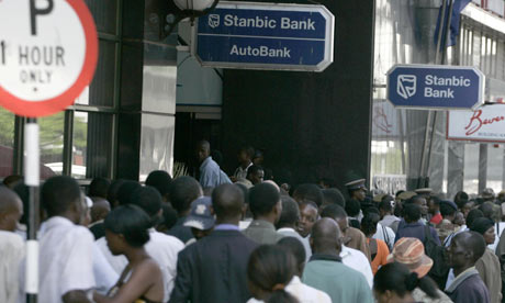 People line up to withdraw cash from local banks in Harare