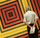 A member of the public walks past the painting 'Jacques le Fataliste' by Frank Stella