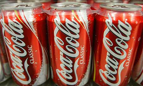 Cans of Coca-Cola sit on the shelf.