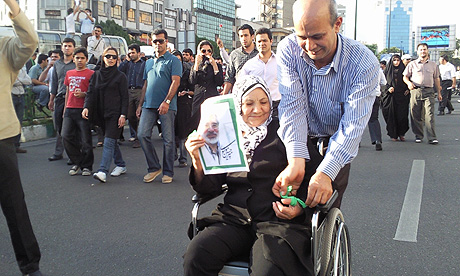 A supporter of Mir Hossein Mousavi has a piece of green cloth tied to her thumb as a rally takes place in Tehran