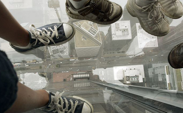 "Children look down the glass floor of ""the ledge"