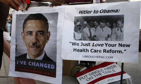 Posters comparing Barack Obama to Adolf Hitler are taped to a table at a town hall meeting on healthcare in Alhambra, California.