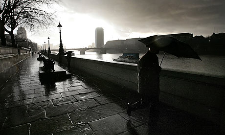 A man walks in the rain along the Albert Embankment in London