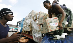 Aid workers offload supplies for people in Harare