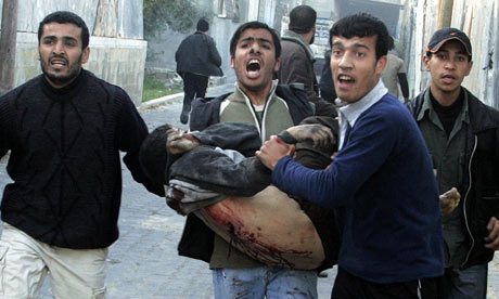A wounded Palestinian is carried near United Nations school in Jabalya