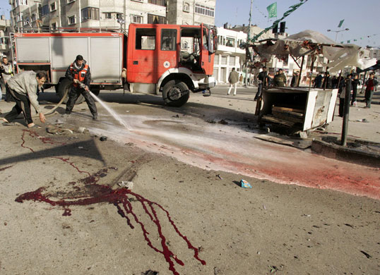 Gallery Gaza: Palestinian firefighter uses hose to clean blood in Gaza