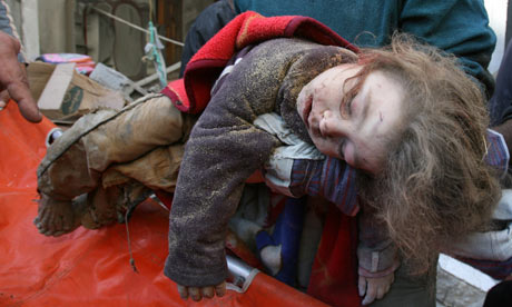 The body of a child is removed from a house in Zeitun