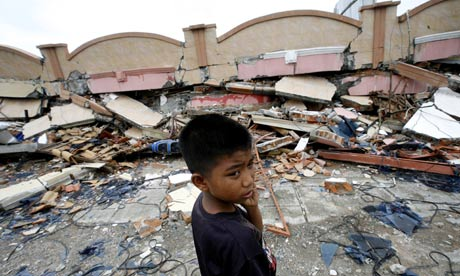 A boy stands near a building flattened by an earthquake in Padang, Sumatra, Indonesia