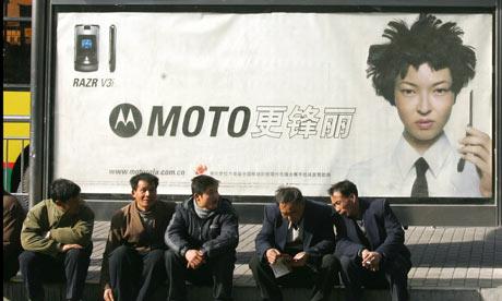 Men sit on the sidewalk in front of a Motorola advertising billboard in Beiijng, China